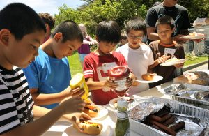 Japanese children from Chatan Town elementary schools, enjoy hotdogs for lunch at the Youth Center during a visit on Kadena Air Base, Japan, July 23, 2015. During the visit, Japanese and American children played ping pong, and other games, and ate an American style lunch together in an effort to learn more about American culture and language. (U.S. Air Force photo by Naoto Anazawa)